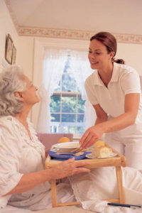 a woman in bed with breakfast and caregiver serving